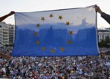 Manifestantes concentrados em frente ao parlamento grego seguram bandeira da União Europeia 18/06/ 2015.  REUTERS/Yannis Behrakis