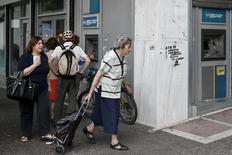 A woman pulls a shopping cart in front of a National Bank of Greece branch in Athens, Greece June 19, 2015. REUTERS/Alkis Konstantinidis