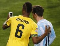 """El jugador jamaiquino, DeShorn Brown, se toma una selfie con el argentino Lionel Messi, al finalizar su partido de la fase de grupos de la Copa América 2015, en el Estadio Sausalito en Viña del Mar, Chile, 20 de junio de 2015. El astro de la selección argentina Lionel Messi está acostumbrado al afecto de hinchas, famosos y hasta otros futbolistas, pero el sábado se mostró sorprendido cuando un jugador jamaiquino se sacó una """"selfie"""" con él dentro de la cancha a pocos segundos del pitazo final del partido por la Copa América. REUTERS/Rodrigo Garrido"""