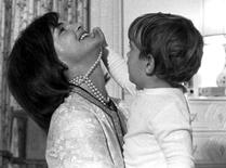 John Kennedy Jr. plays with his mother Jacqueline Kennedy's string of false pearls in this 1962 file photo.  REUTERS/File