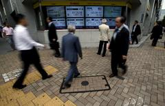 Pedestrians walk past electronic boards showing Japan's Nikkei average (top C L) and the exchange rates between the Japanese yen against the U.S. dollar (top C R) outside a brokerage in Tokyo, Japan, June 23, 2015. REUTERS/Yuya Shino