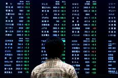 A woman stands in front of a display showing market indices at the Tokyo Stock Exchange (TSE) in Tokyo June 29, 2015. REUTERS/Thomas Peter