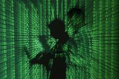 Проекция бинарного кода на мужчину с ноутбуком в Варшаве 24 июня 2013 года. Центральный банк РФ усиливает меры по защите информации в финансовой сфере для оперативного предотвращения хакерских атак на российские банки на фоне всероссийской мобилизации с целью отвратить угрозы извне в эпоху войны санкций. REUTERS/Kacper Pempel
