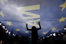 Protesters wave and dance under a huge EU flag during a pro-Euro rally in front of the parliament building, in Athens, Greece, June 30, 2015.  REUTERS/Yannis Behrakis