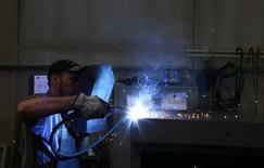 Un trabajador soldando en una fábrica en Gravellona Lomellina, al suroeste de Milán, 11 de junio de 2013. La actividad manufacturera global se desaceleró el mes pasado ya que la mayoría de las economías asiáticas se mantuvieron débiles mientras que las negociaciones sobre la deuda de Grecia pesaron sobre la producción de la zona euro, mostró un sondeo el miércoles. REUTERS/Stefano Rellandini
