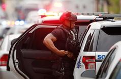 Сотрудник полиции в Вашингтоне 2 июля 2015 года. Штаб-квартира командования кораблестроения и вооружений военно-морских сил США в Вашингтоне оцеплена из-за предполагаемого проникновения туда вооруженного человека, сообщила полиция. REUTERS/Jonathan Ernst