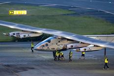 Crew members push the solar-powered plane Solar Impulse 2 to its parking position at Nagoya airport after changing weather conditions thwarted a planned take-off, June 24, 2015.  REUTERS/Thomas Peter