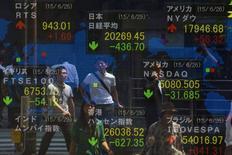 Personas de pie frente a un tablero electrónico que muestra el índice Nikkei, en Tokio, 29 de junio de 2015. El índice Nikkei de la bolsa de Tokio subió el viernes, recortando pérdidas anteriores gracias a las ganancias de las acciones del sector bancario, aunque la cautela antes de un referendo el fin de semana en Grecia limitó la acción general. REUTERS/Thomas Peter