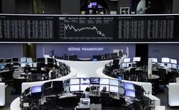 Traders are pictured at their desks in front of the DAX board at the Frankfurt stock exchange July 2, 2015.     REUTERS/Remote/Staff