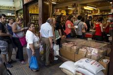 """Personas hacen fila para comprar en una tienda en Atenas, 3 de julio de 2015. Grecia podría librarse de las batallas, que en el caso de Argentina duraron una década, si termina reestructurando su deuda, aunque expertos legales dicen que de todas formas los fondos """"buitres"""" podrían tratar de coaccionar a Atenas. REUTERS/Marko Djurica"""