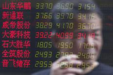 An investor is reflected on an electronic board showing stock information at a brokerage house in Shanghai, China, July 3, 2015. REUTERS/Aly Song