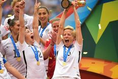 Jul 5, 2015; Vancouver, British Columbia, CAN; United States defender Meghan Klingenberg (22) reacts as teammate United States midfielder Megan Rapinoe (15) hoists the FIFA Women's World Cup trophy  after defeating Japan in the final of the FIFA 2015 Women's World Cup at BC Place Stadium.  Anne-Marie Sorvin-USA TODAY Sports