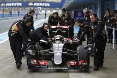 Lotus Formula One racing driver Pastor Maldonado of Venezuela sits in his car as he is pushed by members of his team during pre-season testing at the Jerez racetrack in southern Spain February 3, 2015. REUTERS/Marcelo del Pozo