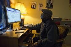 Liberian-American Moses Jensen, founder of the organization Immigrant Information Center, checks his email at his apartment in the Clifton neighborhood of Staten Island, New York October 25, 2014. REUTERS/Darren Ornitz