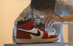 """A visitor photographs an Air Jordan I during a preview for """"The Rise of the Sneaker Culture"""" exhibit at the Brooklyn Museum in the Brooklyn borough of New York, July 8, 2015. REUTERS/Brendan McDermid"""