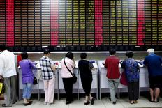La mayoría de las bolsas de Asia borraban sus pérdidas iniciales y subían el jueves al repuntar las accioens chinas y alejarse el  yen de sus recientes máximos. En la foto, unos inversores miran a pantallas electrónicas en una sociedad de valores en Shanghai el 8 de julio de 2015. REUTERS/Aly Song