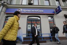 People pass by an office of Promsvyazbank in Moscow, October 4, 2012. Promsvyazbank (PSB), one of Russia's largest privately owned lenders, revealed the details of its initial public offering (IPO) both in Moscow and London in a deal seen as a test for equity raising by other domestic banks. REUTERS/Maxim Shemetov (RUSSIA - Tags: BUSINESS) - RTR38SEJ