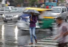 A man holds an umbrella and a teapot as he walks through a busy road during a rain shower in Ahmedabad, India, June 24, 2015. This year's monsoon rains in India are officially forecast to be only 88 percent of the long-term average. REUTERS/Amit Dave