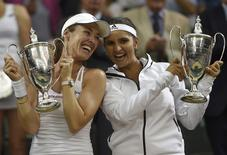 Martina Hingis of Switzerland and Sania Mirza of India pose with their trophies after winning their Women's Doubles Final match against Elena Vesnina and Ekaterina Makarova of Russia at the Wimbledon Tennis Championships in London, July 11, 2015.   REUTERS/Toby Melville