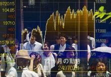Personas se reflejan en un tablero electrónico que muestra los índices de mercado en Tokio, 10 de julio de 2015. El euro operaba estable el lunes después de ceder más temprano y las bolsas de Asia subían mientras los líderes europeos continuaban las negociaciones para alcanzar un acuerdo sobre Grecia. REUTERS/Thomas Peter