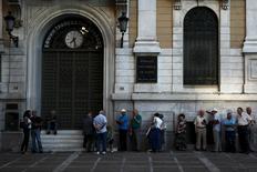 Люди в очереди в отделение National Bank в Афинах 20 июля 2015 года. Греческие банки в понедельник открылись после трех недель простоя, что стало первым признаком возвращения к нормальной жизни после заключения соглашения о начале переговоров о новой программе помощи в обмен на реформы. REUTERS/Yiannis Kourtoglou