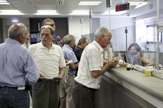 People make transactions at a counter inside a Piraeus Bank branch at the city of Iraklio in the island of Crete, Greece July 20, 2015.  REUTERS/Stefanos Rapanis