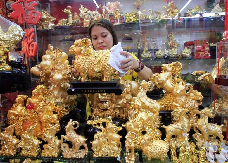 A saleslady wipes off dust on a golden goat statuette for sale for 2,000 pesos ($45.45) a piece at a store in Chinatown in Manila February 3, 2015. REUTERS/Romeo Ranoco/Files