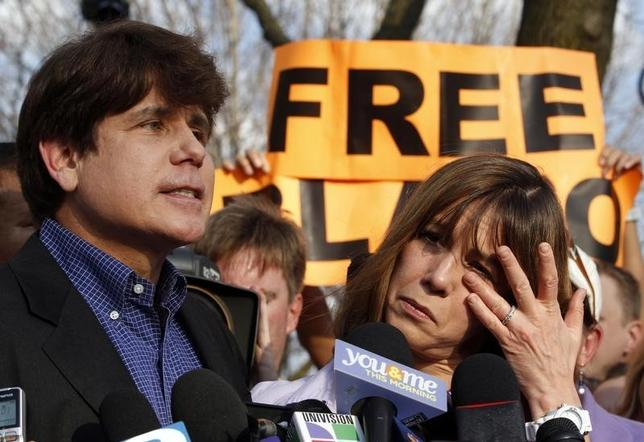 Former Illinois Governor Rod Blagojevich makes a statement to reporters outside his Chicago home one day before reporting to federal prison in Colorado to serve a 14-year sentence for corruption as his wife Patti wipes away tears, March 14, 2012. REUTERS/Jeff Haynes