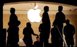 Посетители не фоне логотипа Apple в магазине компании в Нью-Йорке 21 июля 2015 года. Акции Apple Inc рухнули примерно на 7 процентов после закрытия основных торгов вслед за объявлением компанией прогноза выручки в четвертом квартале, который не дотянул до ожиданий аналитиков. REUTERS/Mike Segar