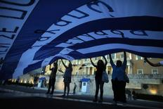 Anti-austerity demonstrators hold up a giant Greek flag in front of parliament in Athens, July 22, 2015.   REUTERS/Ronen Zvulun