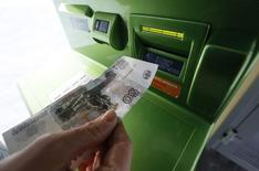 A woman inserts a 50-rouble banknote into an ATM bank machine at a branch of Sberbank in Krasnoyarsk, Siberia, January 27, 2015.Рубль начал торги четверга небольшим подорожанием к доллару за счет продаж валюты перед ключевыми налогами июля и частичной фиксации прибыли в длинных валютных позициях по достижении долларом накануне вечером двухнедельных пиков.  REUTERS/Ilya Naymushin