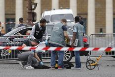 French police look for clues after a car drove through barriers set up for the final stage of the Tour de France in central Paris, France, July 26, 2015. Police opened fire on a car which drove through barriers after refusing to obey them near the Place de la Concorde, Paris police said. Hundreds of thousands of people were expected to gather in the Place de la Concorde and along Champs Elysees avenue for the final leg of the Tour de France later in the day.  REUTERS/Stephane Mahe