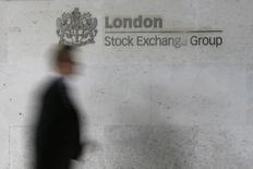 Мужчина проходит мимо здания Лондонской фондовой биржи 11 октября 2013 года. Европейские фондовые рынки растут благодаря квартальным отчетам компаний и сделке производителей цемента HeidelbergCement и Italcementi. REUTERS/Stefan Wermuth