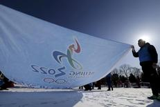 Participants hold a flag bearing the bidding logo of Beijing 2022 Winter Olympics, during a event to gather signatures to support Beijing's bid, at a park in Beijing, China, February 8, 2015.  REUTERS/Stringer