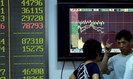 Inversores hablan frente a una pantalla que muestra la información de las acciones, en una correduría en Hangzhou, China, 3 de agosto de 2015. Las acciones en Shanghái cayeron el lunes cuando una encuesta reveló una débil actividad del sector fabril chino y algunos inversores se abstuvieron de participar después de que los valores en la parte continental de China sufrieron en julio su peor pérdida mensual en seis años. REUTERS/China Daily