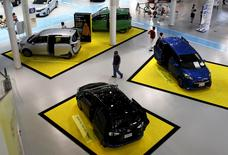 A visitor walks between Toyota Motor Corp's cars displayed at the company's showroom in Tokyo, Japan, August 4, 2015. REUTERS/Yuya Shino
