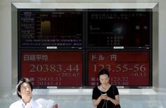 Personas frente a un tablero electrónico que muestra el índice Nikkei y la tasa cambiaria entre el yen japonés y el dólar estadounidense, afuera de una correduría en Tokio, 14 de julio de 2015. Las bolsas de Asia extendían sus ganancias el martes, mientras los inversores hacían caso omiso a unos datos económicos pesimistas reportados en la sesión anterior, centrándose en cambio en un reporte de empleo en Estados Unidos que podría dar señales sobre el momento en que la Reserva Federal comenzará a subir las tasas de interés. REUTERS/Toru Hanai