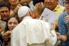 Pope Francis greets a child as he arrives to lead his weekly audience in Paul VI hall at the Vatican City, August 5, 2015. REUTERS/Giampiero Sposito