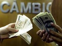 Una persona cambia reales brasileños por dólares en una casa de cambio en el centro de Río de Janeiro, 4 de agosto de 2003. Las monedas de mercados emergentes probablemente anoten nuevos mínimos en los próximos meses mientras China actúa para contener la volatilidad del mercado y Estados Unidos se acerca a subir las tasas de interés por primera vez en casi una década, mostró un sondeo de Reuters. Reuters/Bruno Domingos