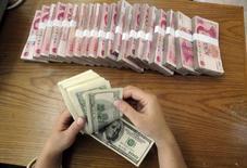 Работник отделения Bank of China считает деньги. Хэфэй, 16 октября 2009 года. Валютные резервы Китая, крупнейшие в мире, сократились в июле на $42,5 миллиарда, до $3,65 триллиона, свидетельствуют данные Центробанка, опубликованные в пятницу. REUTERS/Stringer