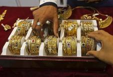Продавец помогает покупателю выбрать золотой браслет в ювелирном магазине в Мумбаи. 21 мая 2015 года. Рынок золота готовится завершить спадом седьмую неделю подряд, чего не случалось с 1999 года, в ожидании отчета о занятости в США, который повлияет на срок повышения процентных ставок ФРС. REUTERS/Shailesh Andrade