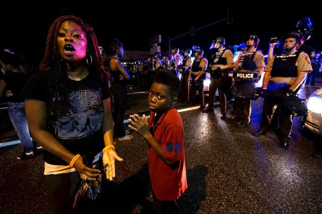 Amarion Allen, 11-years-old (C), and his mother Amima stand in front of a police line shortly before shots were fired in a police-officer involved shooting in Ferguson, Missouri August 9, 2015. REUTERS/Rick Wilking