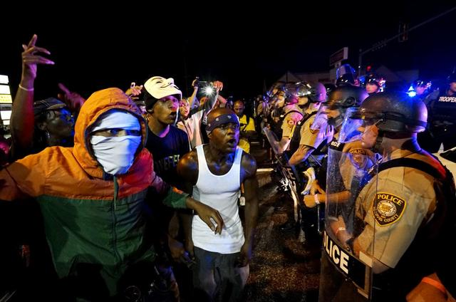 Protesters yell at a police line shortly before shots were fired in a police-officer involved shooting in Ferguson, Missouri August 9, 2015.  REUTERS/Rick Wilking