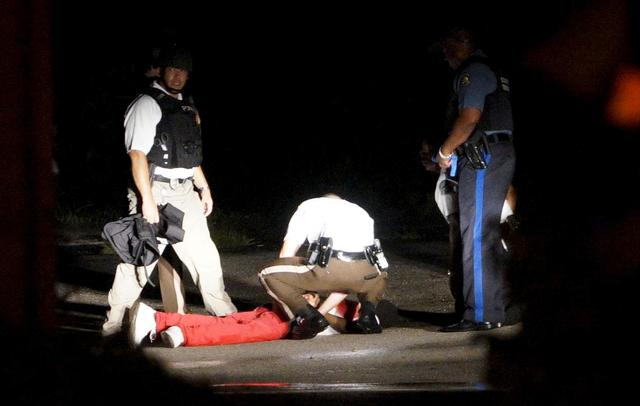 A black man lies badly wounded with blood on his shirt after a police officer involved shooting in Ferguson, Missouri August 9, 2015. REUTERS/Rick Wilking
