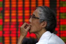 Un inversor mira un tablero electrónico que muestra la información de las acciones en una correduría en Shanghái, China, 10 de julio de 2015. Las bolsas chinas cerraron con desempeños dispares el martes luego de que la sorpresiva decisión del banco central de permitir que el yuan se depreciara golpeó a las acciones de las aerolíneas y los importadores, pero impulsó a los exportadores. REUTERS/Aly Song
