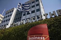 Una bandera griega flameando a las afueras de la bolsa en Atenas, jul 27 2015. La economía de Grecia regresó inesperadamente al crecimiento en el segundo trimestre pese a la inestabilidad política y a la amenaza de una salida del país de la zona euro, según mostraron el jueves datos oficiales.  REUTERS/Ronen Zvulun
