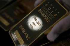 Imagen de archivo de un empleado del mercado de oro de Corea del Sur con una barra de un kilo del metal precioso en sus manos, jul 31 2015. El oro bajó ligeramente el viernes, después de que el dólar cambió de tendencia y subió tras conocerse datos económicos alentadores en Estados Unidos. REUTERS/Kim Hong-Ji