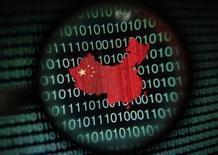 """Un mapa de China, visto a través de una lupa, en la pantalla de un computador que muestra digitos binarios, en Singapur, ilustración fotográfica, tomada el 2 de enero de 2014. La policía de China dijo el martes que arrestó a cerca de 15.000 personas por delitos que """"ponen en peligro la seguridad de internet"""", en momentos en que el Gobierno busca reforzar los controles en la red. REUTERS/Edgar Su/Files"""