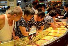 Покупатели в ювелирном магазине в городе Сюйчан в китайской провинции Хэнань. 12 августа 2015 года. Цена на золото стабильна во вторник, так как внимание инвесторов вернулось к возможному повышению ставок ФРС США. REUTERS/Stringer