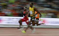 Mike Rodgers of the U.S. (L) and Usain Bolt of Jamaica (C) competes in the men's 100 metres heats during the 15th IAAF World Championships at the National Stadium in Beijing, China August 22, 2015.  REUTERS/Phil Noble